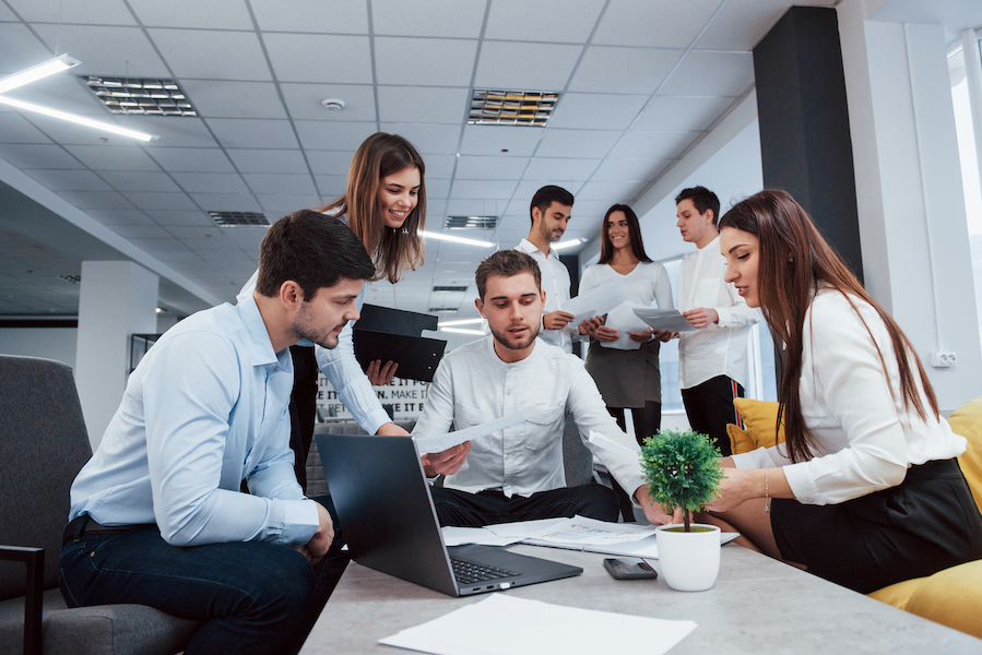 Making business plan. Group of young freelancers in the office have conversation and smiling