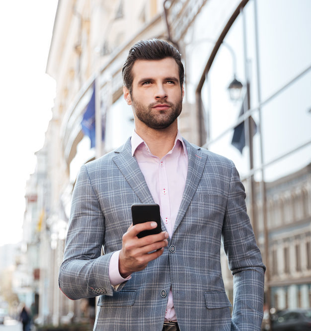 Handsome man in a jacket walking and holding mobile phone